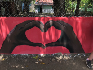 a hand painted mural of two hands shaping a heart made by a group of volunteers from montgomery county, pa on a non-religious mission trip